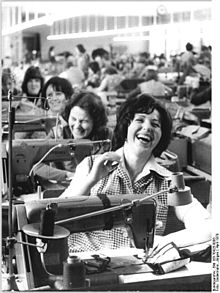 Black and white photo of women laughing in a clothing factory