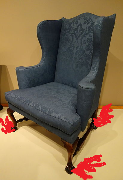 Old fashion blue upholstered wing chair with red wings drawn onto legs.