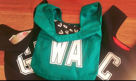 Three netball bib bags. Two black in back and one green Wing Attack bag at front