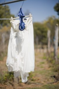 White dress and blue undies hanging on clothes line.