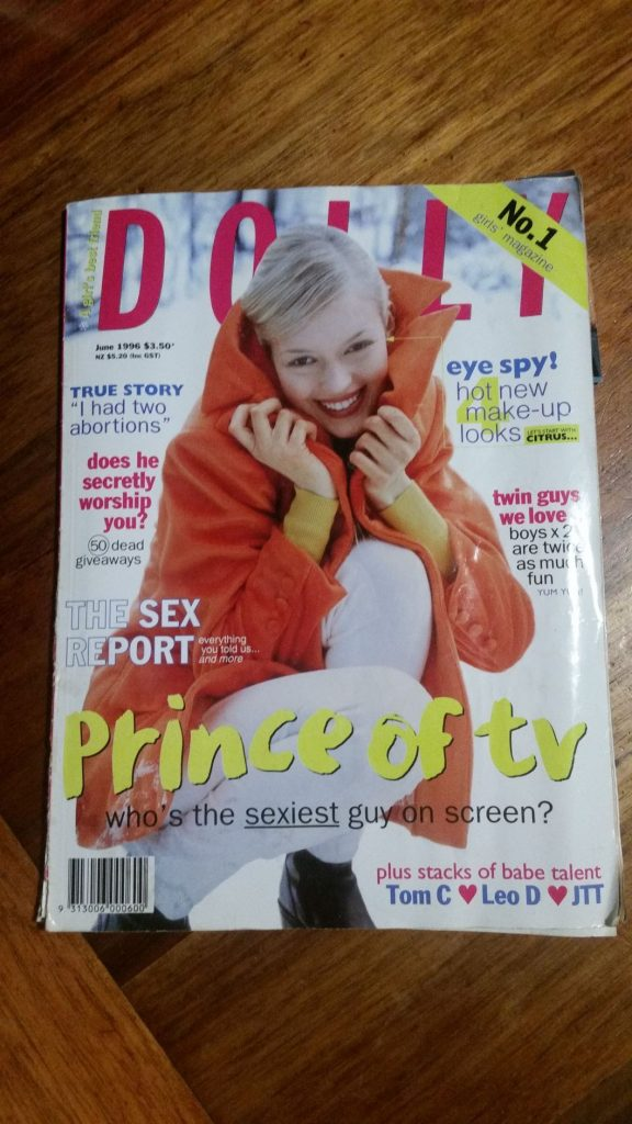 Cover Dolly magazine. Woman with blonde hair crouching wearing an orange jacket.