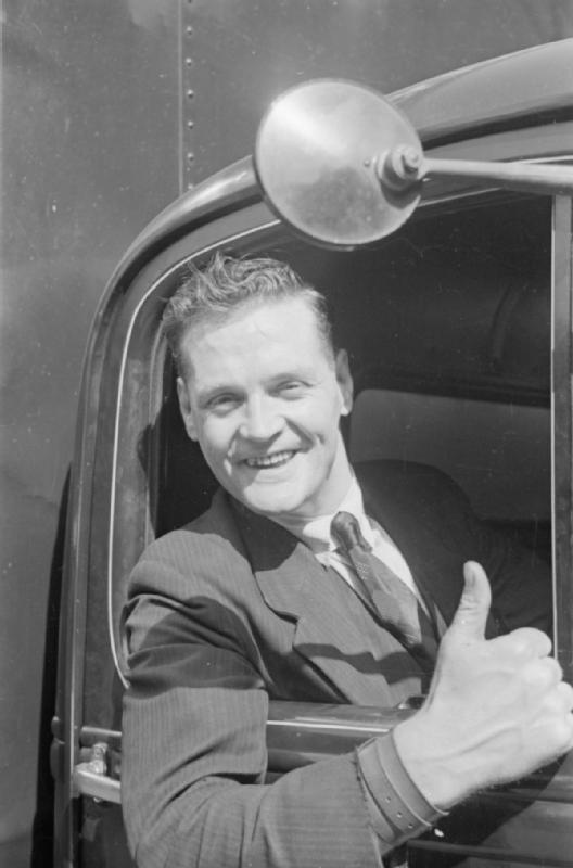 Black and white photo of a man in a truck giving a thumbs up signal