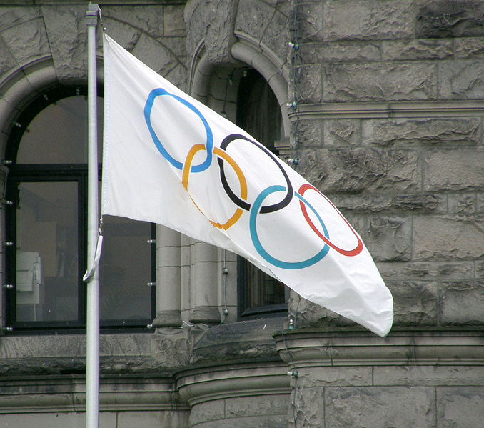 Olympic flag in front of a grey stone building