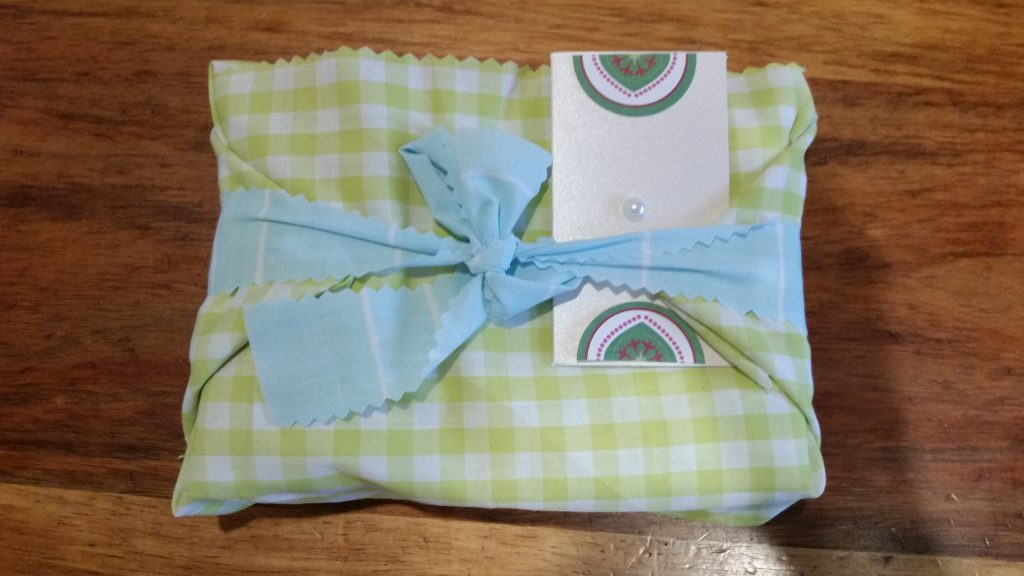 Gift in green and white checked material with a blue bow. White card.